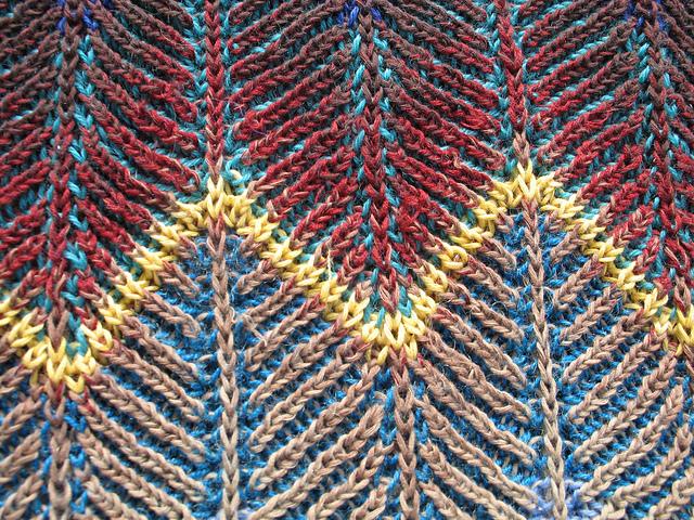 Hier kann man Mottenfraß an herausstehenden Fäden erkennen, hauptsächlich im Rot und im Beige