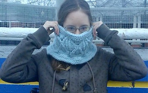 A woman holding a bulky-weight knit cowl over her mouth and nose