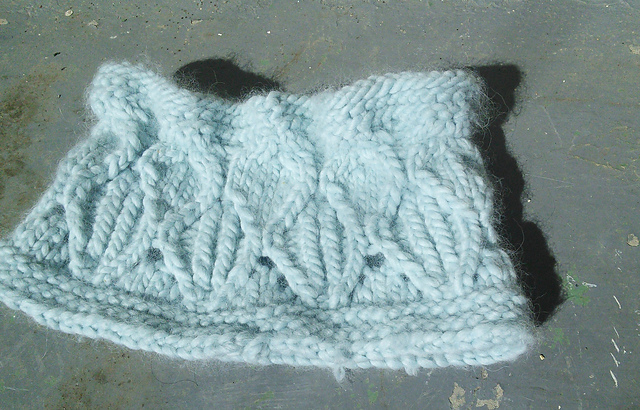 Image Description:  A lace and cable cowl worked in a bulky-weight pale blue yarn, laying flat on a concrete surface.