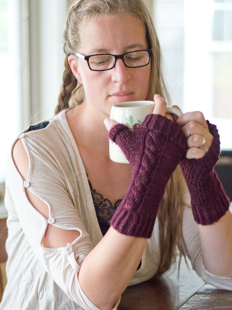 woman drinking coffee wearing fingerless mitts