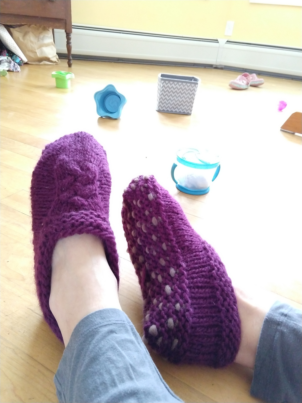 two feet in slippers one showing the sole