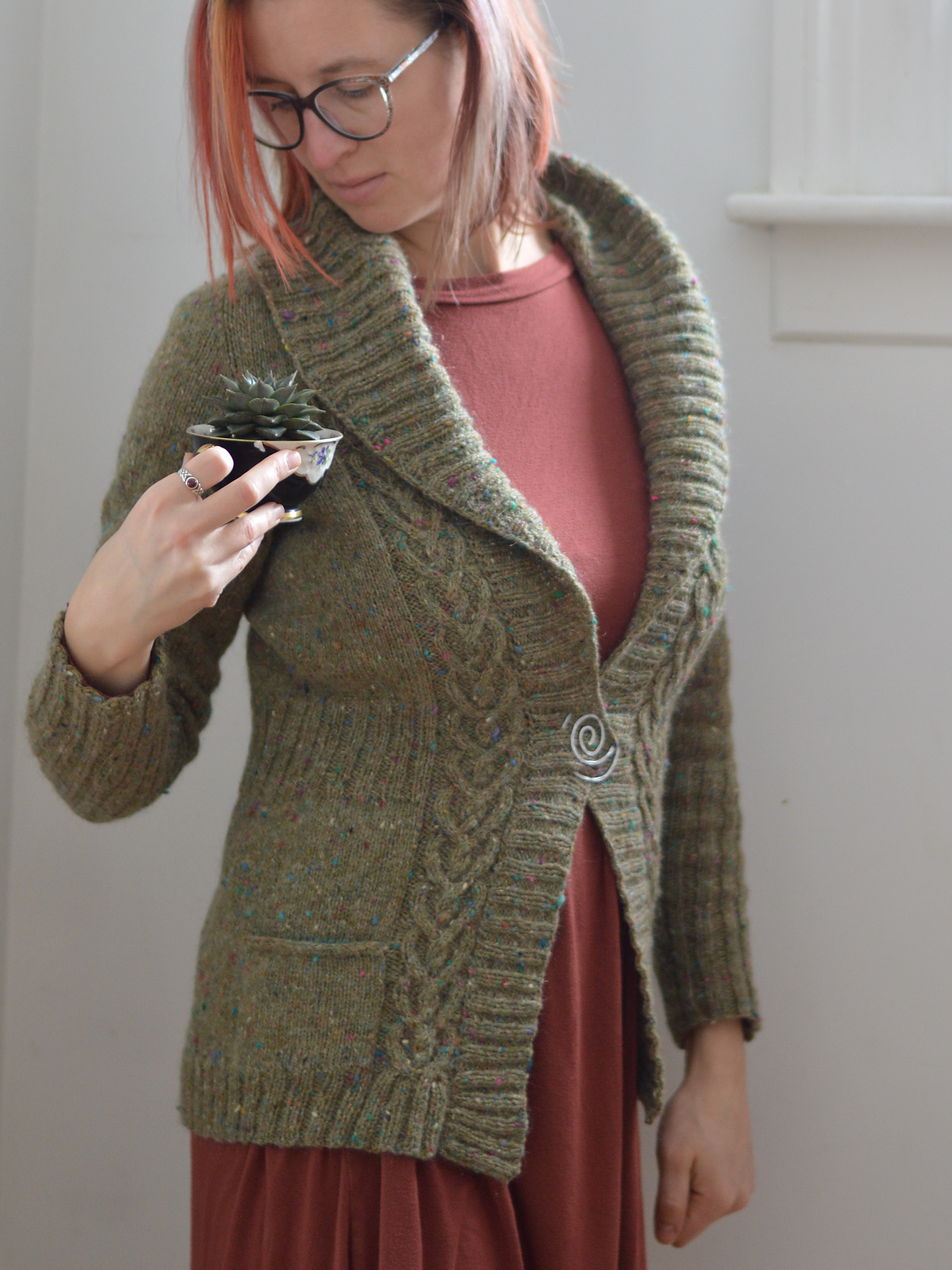 side view of a woman in an olive sweater with cable details