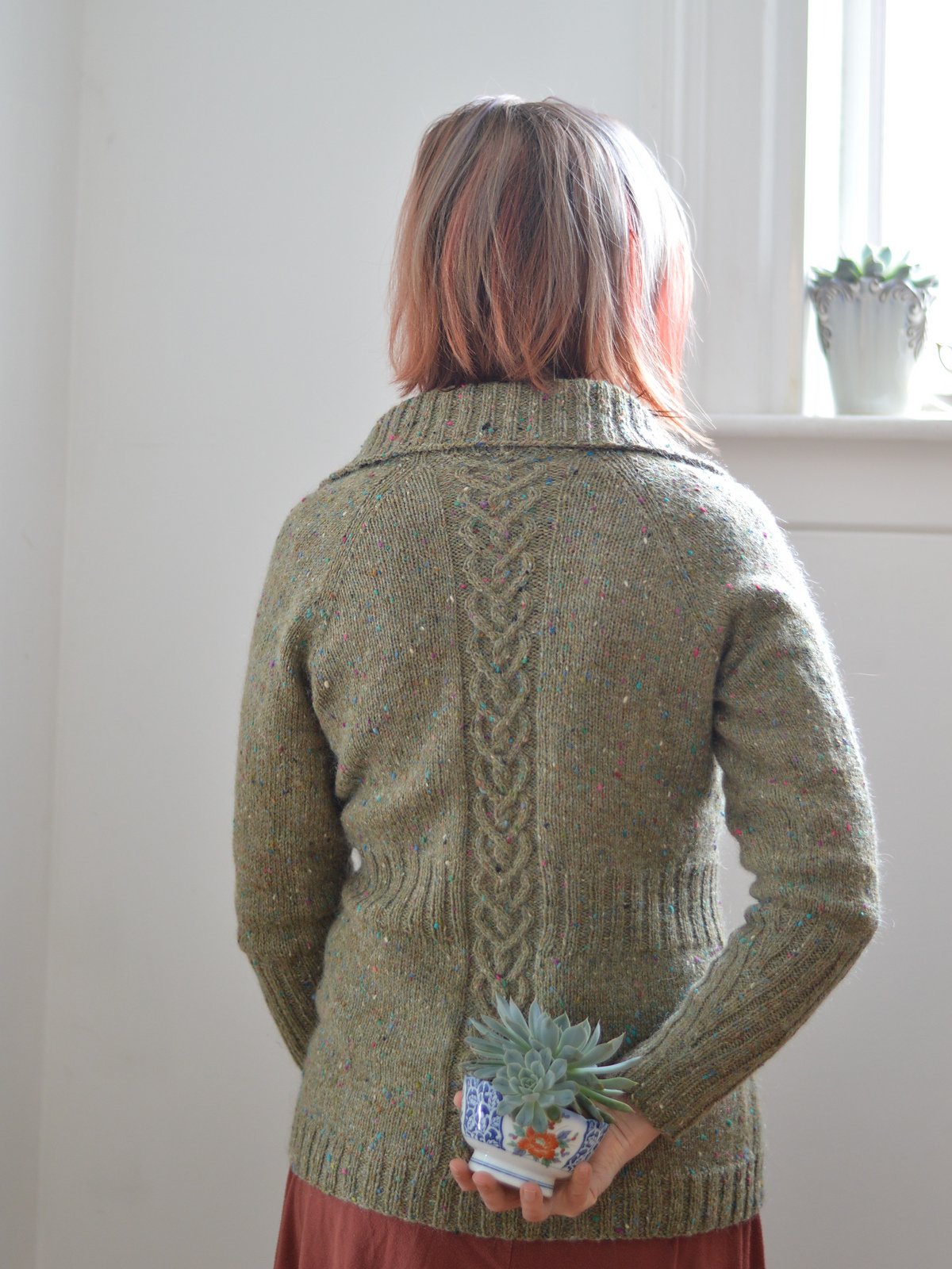 back view of a woman in an olive sweater with cable details