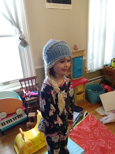 girl in knitted hat with braid attached to brim