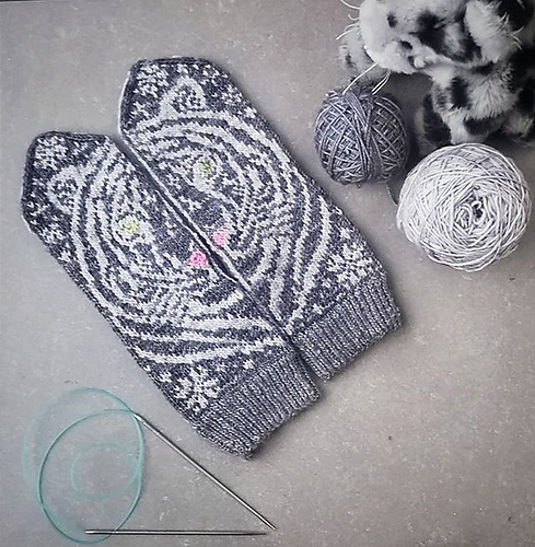 Two grey mittens with a tiger design shown when they are put side by side