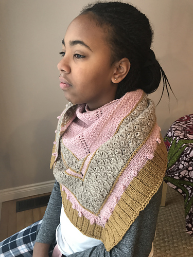 A girl with her hair pulled back wears a shawl made with pink and gold yarn