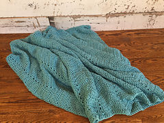 Cozy_comforts_blanket_crochet_pattern_on_wood_table_close_small