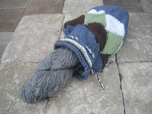 A drawstring bag made primarily of joined mitered squares. The top has eyelets with a twisted cord threaded through them, and a skein of yarn is partially out of the open bag.]