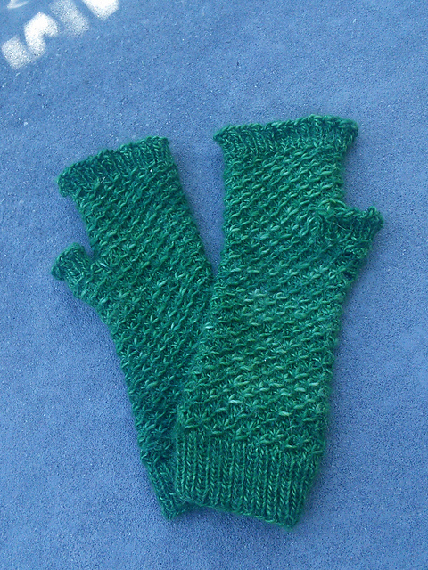 A pair of fingerless mittens laying flat and slightly overlapping.