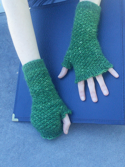Someone wearing a pair of fingerless mittens. The mittens are knit in a dark green fingering-yarn and use a textured star stitch over the body of the mitten.