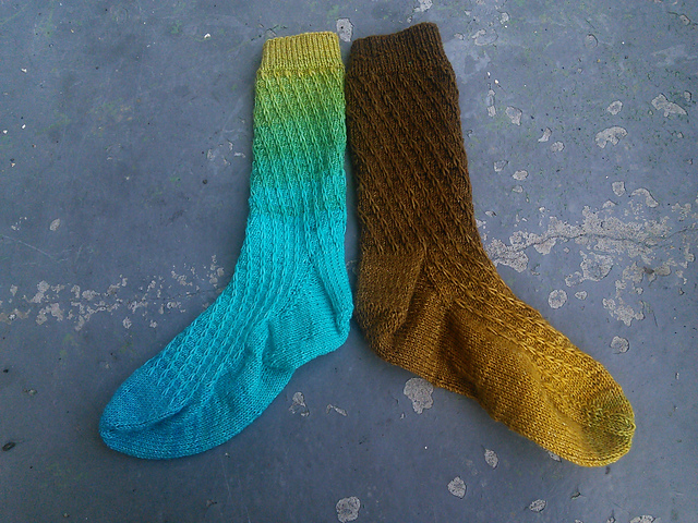 A pair of socks knit in a gradient yarn.  One sock is a brown-tan-yellow ombre, while the other sock is a yellow-green-blue ombre.