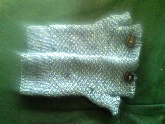 A pair of textured fingerless mittens knit in blue-grey yarn, with a single wooden button on each of the top cuffs.