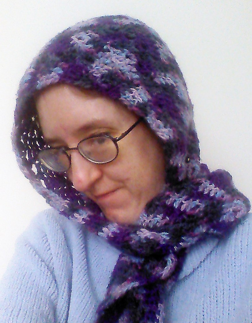 [A woman wearing a hood with a scarf.  The hood is done in worsted-weight crochet in a chevron pattern.  The yarn is variegated yarn that runs between purple, black, and grey.
