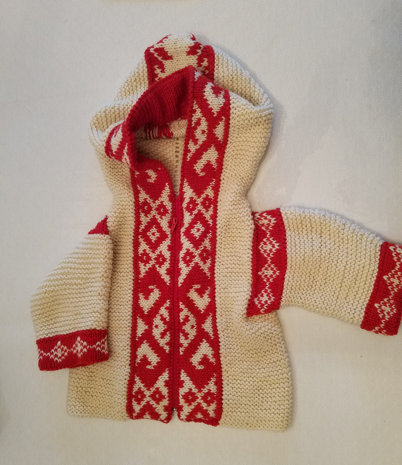 Small knit white sweater with a red and white patterned border
