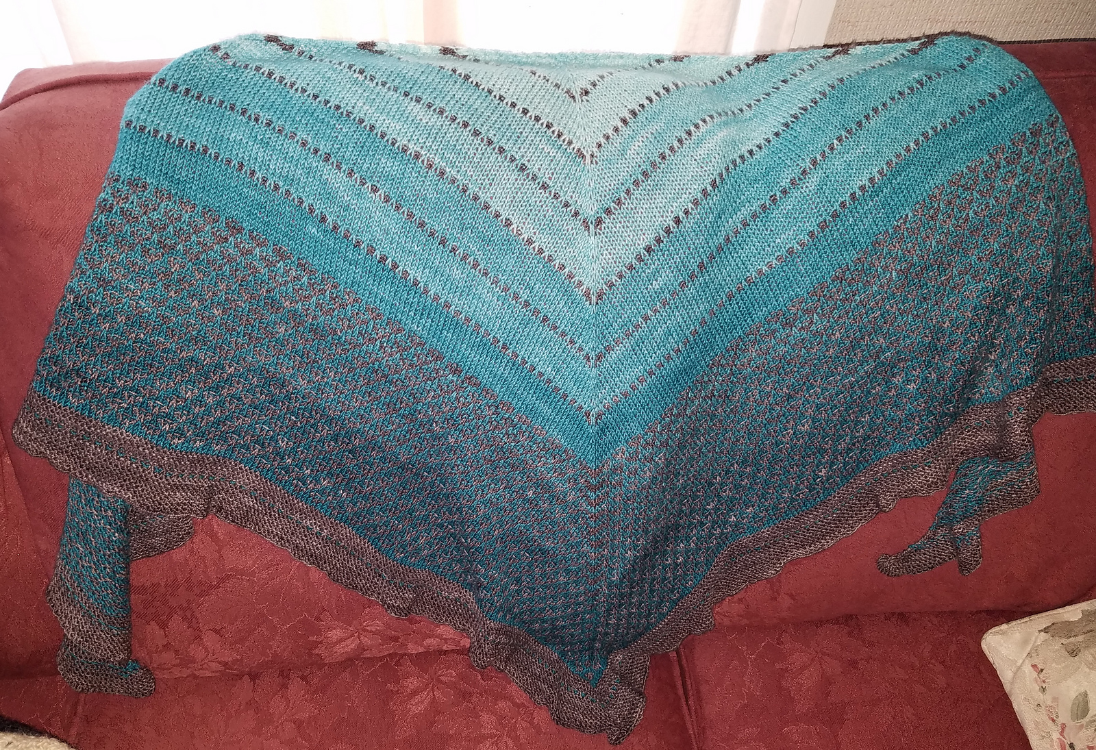 A knit shawl in stripes alternating between grey-brown and light blue deepening to darker blue