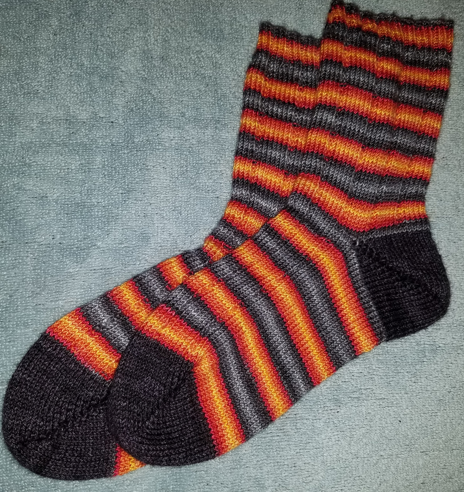 A pair of striped socks, alternating between a red-and-yellow stripe and a black-and-grey stripe