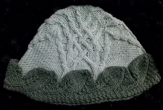 Knit hat with light green cabled trees and darker green leaf borrder