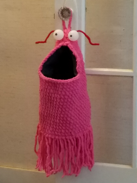 A fuzzy pink bag with googly eyes and antenna