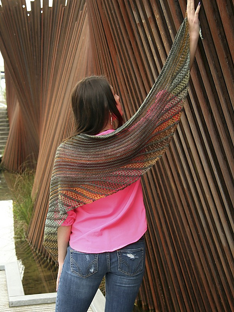 A lady in front of a wooden wall, holding up her right arm to display her colorfully striped autumn colored shawl with lacy edges