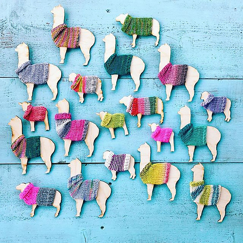 a group of wooden sheep and llamas all wearing little handknit sweaters, on a blue background