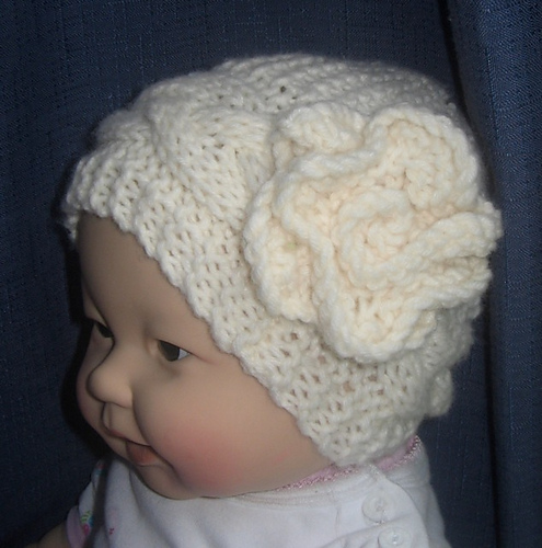 36460a066c1 Ravelry  Cable Hat with Flower pattern by Rian Anderson