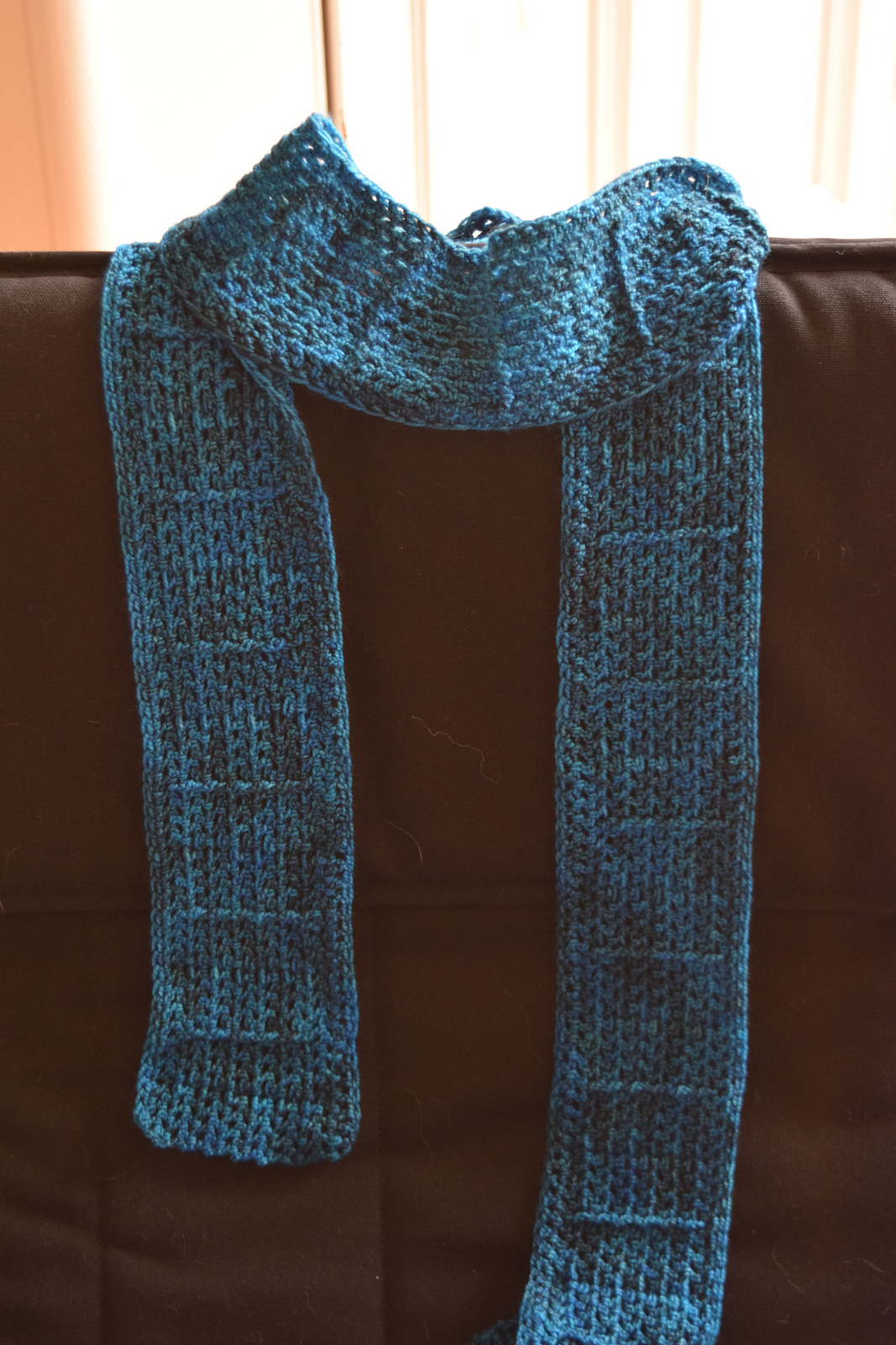 turquoise rectangular ribbed scarf draped over a chair