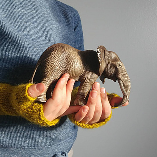 Hands wearing yellow fingerless mitts holding an elephant figurine
